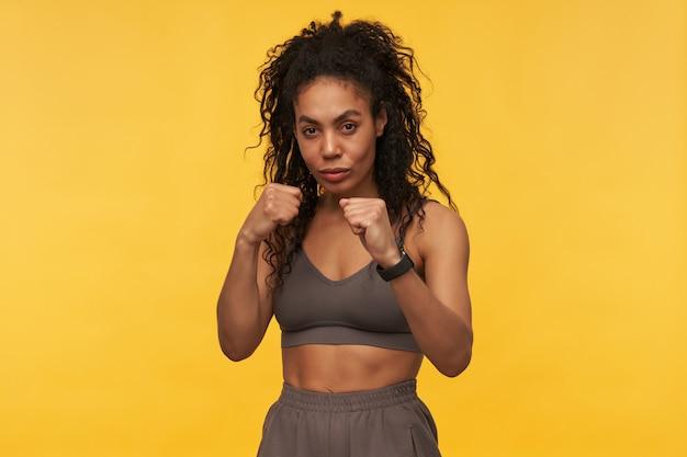 Skoncentrowana, ładna młoda sportowiec trzyma ręce przed sobą i robi boks w cieniu na białym tle nad żółtą ścianą