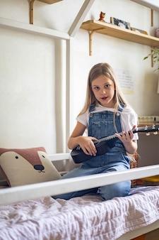 Skoncentrowana mała dziewczynka grająca melodię na ukulele, ćwicząca ćwiczenie muzyczne, ciesząca się nauką edukacyjną