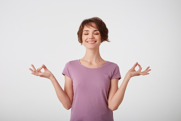 Skoncentrowana młoda atrakcyjna młoda krótkowłosa dama w pustym t-shircie, trzyma ręce w dobrym geście, medytuje w pomieszczeniach, ma zamknięte oczy, próbuje się zrelaksować, odizolowana na białej ścianie.