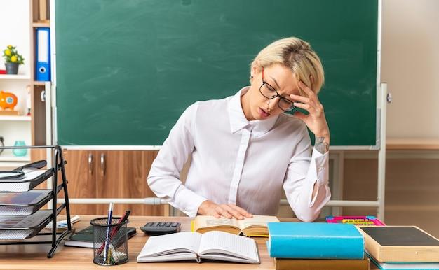 Skoncentrowana młoda blond nauczycielka w okularach, siedząca przy biurku z szkolnymi narzędziami w klasie, trzymająca rękę na głowie i na otwartej książce, czytając książkę