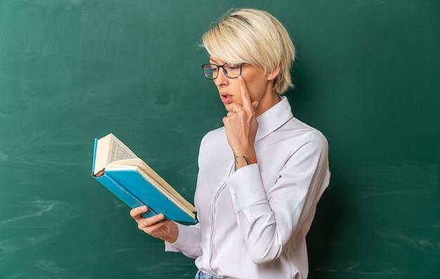 Skoncentrowana młoda blond nauczycielka w okularach w klasie stojąca w widoku profilu przed tablicą trzymającą i czytającą książkę trzymającą rękę na brodzie