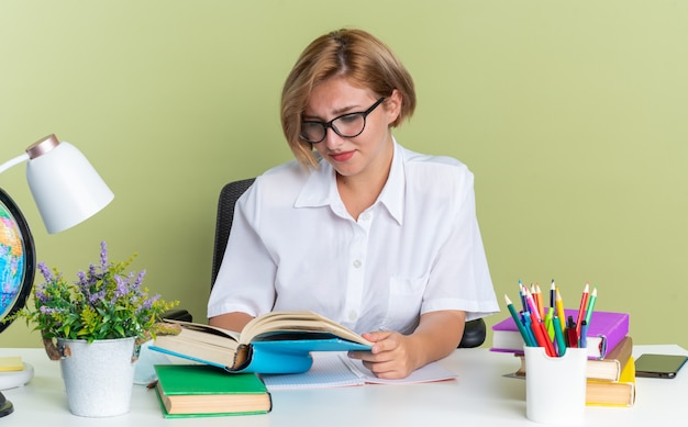 Skoncentrowana młoda blond studentka w okularach siedząca przy biurku z szkolnymi narzędziami, czytająca książkę odizolowaną na oliwkowozielonej ścianie