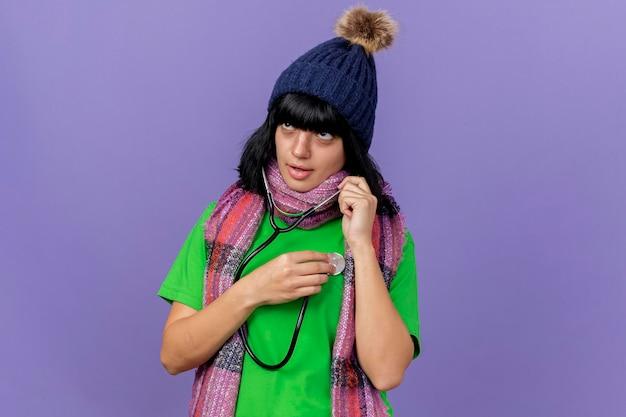 Skoncentrowana młoda chora kobieta w czapce zimowej i szaliku ze stetoskopem patrząc w bok, słuchająca bicia jej serca na fioletowej ścianie z miejscem na kopię