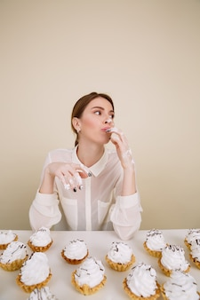 Skoncentrowana młoda dama pozuje podczas gdy jedzący babeczki.