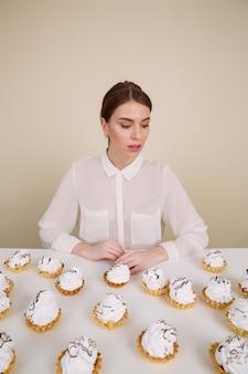 Skoncentrowana młoda dama pozuje podczas gdy siedzący blisko babeczki