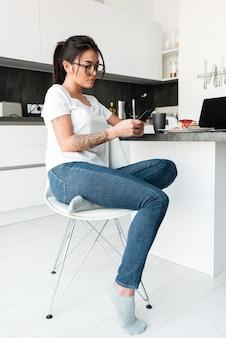 Skoncentrowana młoda dama siedzi w kuchni