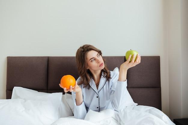 Skoncentrowana młoda dama wybiera między pomarańczą a jabłkiem