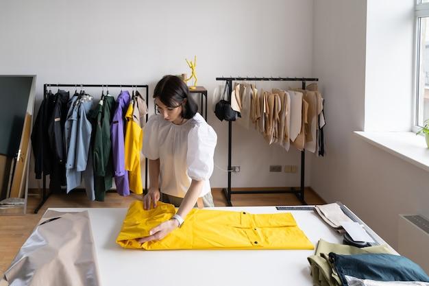 Skoncentrowana młoda dziewczyna hipster krawcowa pracuje nad nową kolekcją płaszczy przeciwdeszczowych w studiu krawieckim