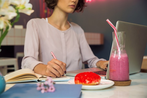 Skoncentrowana młoda dziewczyna pisze notatkach