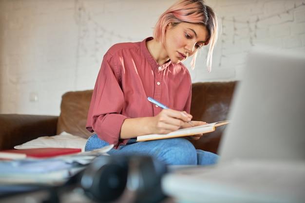 Skoncentrowana młoda kobieta copywriter z różowymi włosami, pracująca w domu, robiąc notatki w zeszycie.
