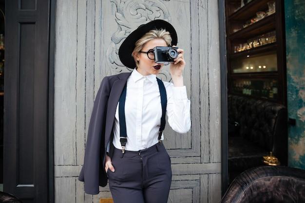 Skoncentrowana młoda kobieta fotograf stojąca i robiąca zdjęcia za pomocą aparatu fotograficznego