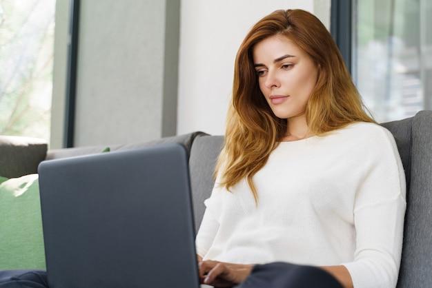 Skoncentrowana młoda kobieta korzystająca ze swojego nowoczesnego laptopa siedząc przy kanapie. ładna dziewczyna imbir sprawdzanie wiadomości siedząc w domu. koncepcja życia domowego
