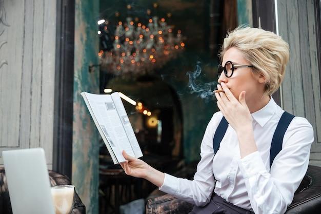 Skoncentrowana młoda kobieta paląca papierosa i czytająca magazyn w kawiarni