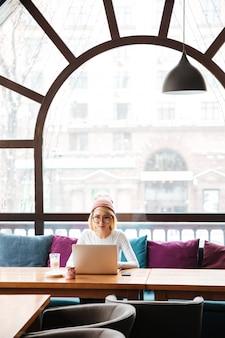 Skoncentrowana młoda kobieta pracuje z laptopem w kawiarni