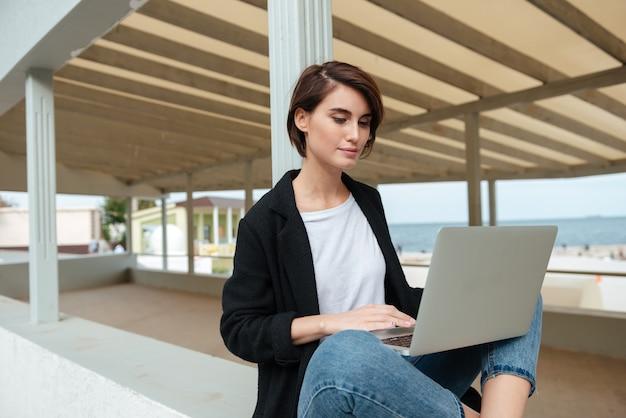 Skoncentrowana młoda kobieta siedzi i używa laptopa w altanie na plaży