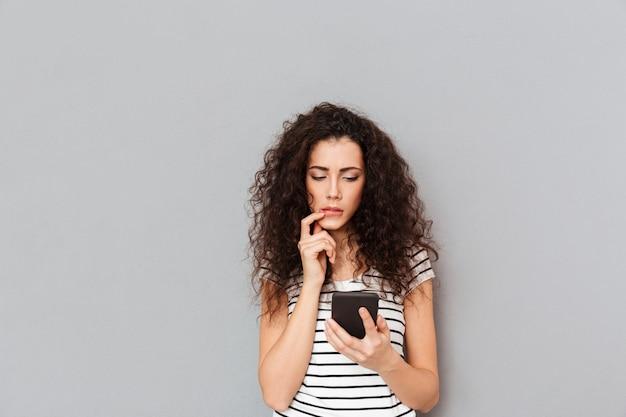 Skoncentrowana młoda kobieta używa smartphone i dotyka jej usta jest sfrustrowana lub otrzymuje złe wieści na szarej ścianie
