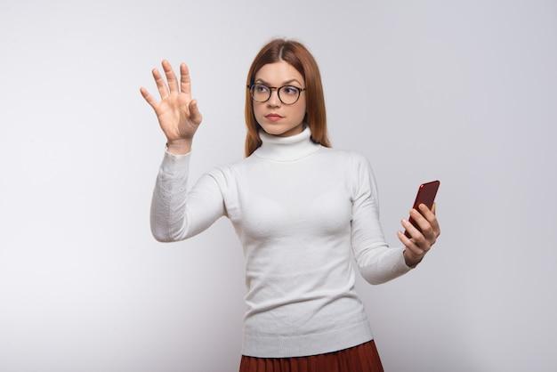 Skoncentrowana młoda kobieta używa smartphone