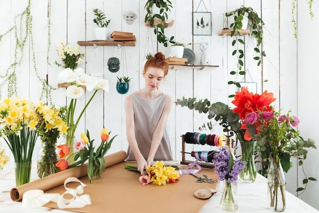 Skoncentrowana młoda kobieta zbiera kolorowego bukiet w warsztacie