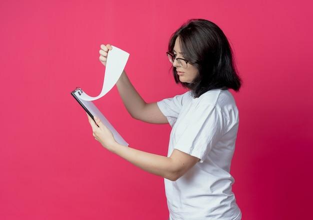 Skoncentrowana młoda ładna kaukaska dziewczyna w okularach stojąca w widoku profilu, trzymając i patrząc na schowek na białym tle na szkarłatnym tle z miejsca na kopię