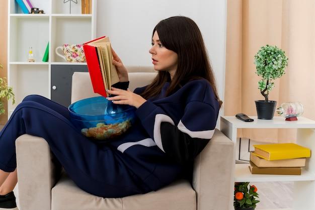 Skoncentrowana młoda ładna kaukaski kobieta siedzi na fotelu w zaprojektowanym salonie trzymając miskę chipsów na nogach i czytając książkę