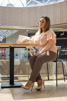 Skoncentrowana młoda plus size kobieta biznesu na czacie korzysta z telefonu komórkowego siedzącego przy stole w biurze wnętrza