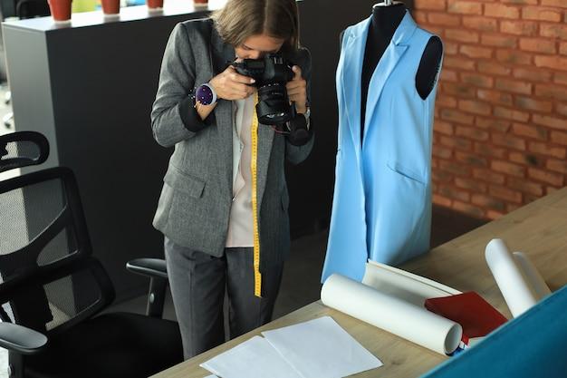 Skoncentrowana młoda projektantka korzystająca z aparatu cyfrowego, stojąc przy biurku w swoim gabinecie kreatywnym.