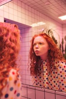 Skoncentrowana młoda rudzielec kędzierzawa dama patrzeje lustro.
