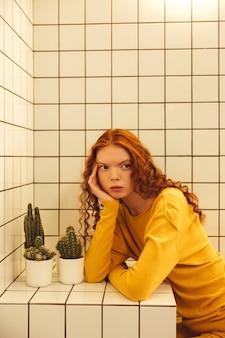 Skoncentrowana młoda rudzielec kędzierzawa dama siedzi w kawiarni