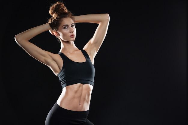 Skoncentrowana młoda sportowa dama stoi nad czerni ścianą