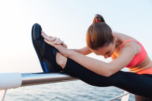 Skoncentrowana młoda spotwoman rozciągająca nogi na świeżym powietrzu w pobliżu morza