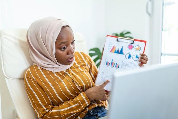 Skoncentrowana muzułmańska bizneswoman przedstawiająca wykresy i wykresy podczas rozmowy wideo online. młoda kobieta biznesu ih hidżab o połączenie konferencyjne z klientem na laptopie. działający laptop kryty.