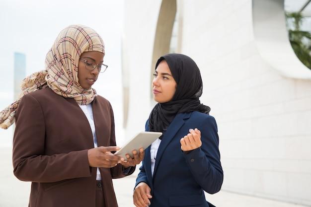 Skoncentrowana muzułmańska kobieta wyjaśniająca specyfikę projektu