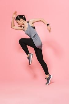 Skoncentrowana, niesamowita, piękna, młoda, ładna kobieta fitness, która biega, wykonuje ćwiczenia sportowe izolowane nad różową ścianą