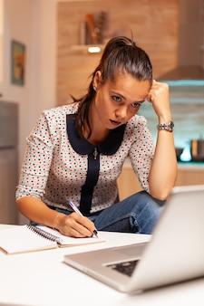 Skoncentrowana niezależna kobieta pracująca w nadgodzinach, aby dokończyć projekt z domowej kuchni. pracownik korzystający z nowoczesnych technologii o północy wykonujący nadgodziny w pracy, biznesie, karierze, sieci, stylu życia, bezprzewodowo