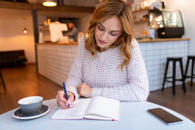Skoncentrowana pozytywna ładna młoda blondynka siedzi w kawiarni w pomieszczeniu, pisząc notatki w notesie.