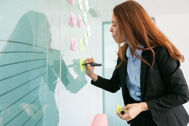 Skoncentrowana rudowłosa bizneswoman pisze na naklejce z markerem