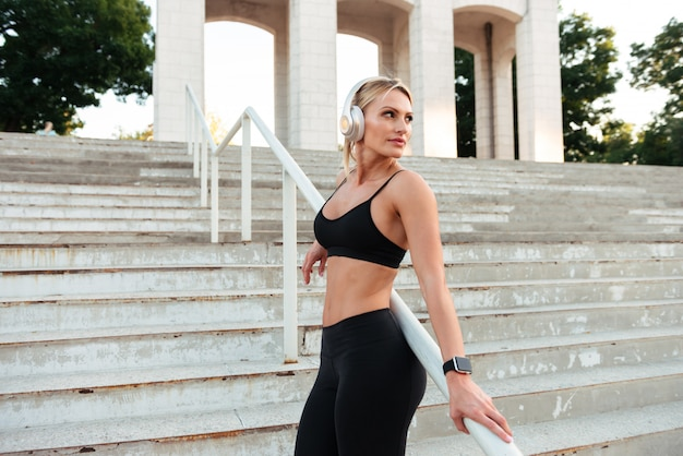 Skoncentrowana silna młoda sportowa kobieta słucha muzykę