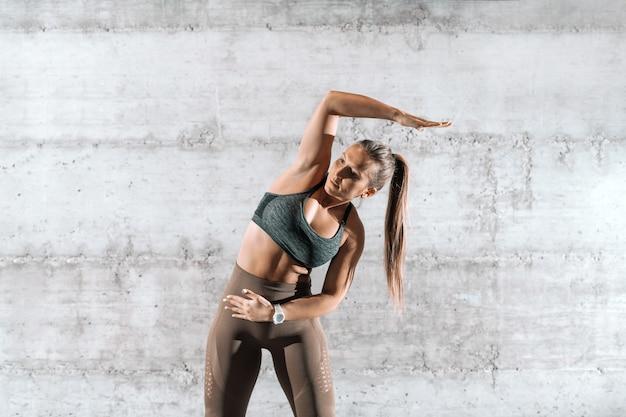 Skoncentrowana, sportowa brunetka z kucykiem i sportową odzieżą rozciągającą ramię przed ćwiczeniami przed szarą rustykalną ścianą.