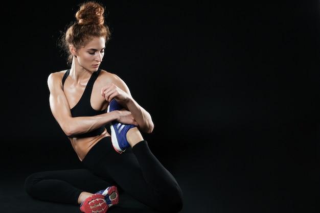 Skoncentrowana sprawności fizycznej kobieta robi ćwiczeniom joga