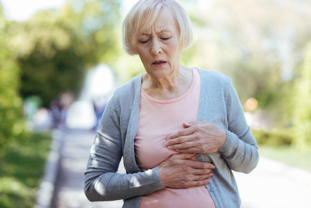 Skoncentrowana stara chora kobieta dotyka swojej klatki piersiowej i wyraża smutek podczas ataku serca na świeżym powietrzu