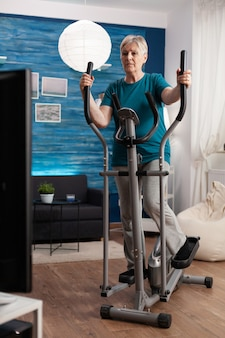 Skoncentrowana starsza kobieta pracująca na mięśniach nóg, wykonująca ćwiczenia ciała za pomocą rowerowej maszyny rowerowej podczas treningu fitness