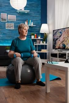 Skoncentrowana starsza kobieta robi ćwiczenia ramion przy użyciu hantli treningowych, siedząc na piłce szwajcarskiej