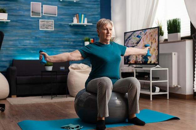 Skoncentrowana starsza kobieta rozciągająca ramię pracująca na mięśnie ciała za pomocą hantli fitness siedzącej na szwajcarską piłkę w salonie. kaukaski mężczyzna ćwiczący mięśniową opiekę zdrowotną podczas treningu wellness
