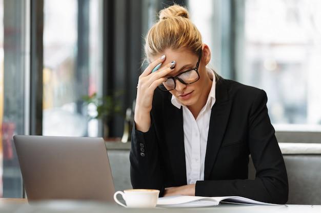 Skoncentrowane biznesowej kobiety writing notatki w notatniku.