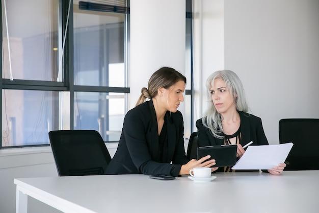 Skoncentrowane koleżanki omawiające i analizujące raporty. dwóch profesjonalistów siedzi razem, trzymając dokumenty, używając tabletu i rozmawiając. koncepcja pracy zespołowej