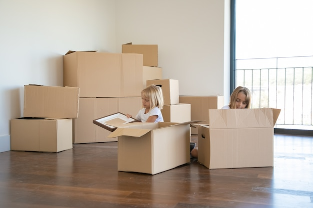 Skoncentrowane małe dzieciaki rozpakowują rzeczy w nowym mieszkaniu, siedzą na podłodze i wyjmują przedmioty z otwartych pudełek z kreskówek