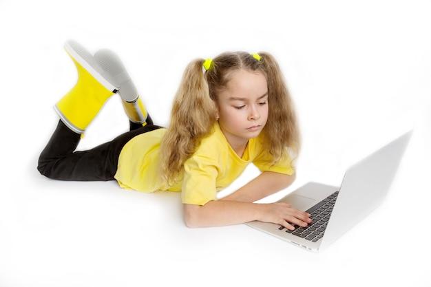 Skoncentrowane małe słodkie europejskie dziecko dziewczyna nosi żółtą koszulkę leżącą przed komputerem, sprawdzając zadania w klasie online, koncepcja e-learningu na odległość.