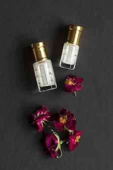 Skoncentrowane perfumy w mini butelce na czarnym stole.