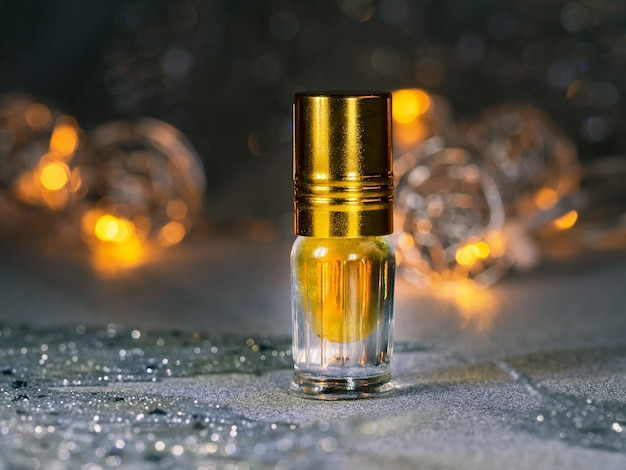 Skoncentrowane perfumy w mini buteleczce na błyszczącym, świątecznym ciemnym tle.