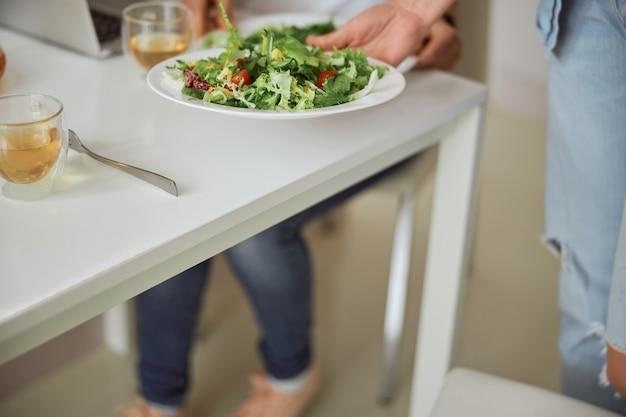 Skoncentrowane zdjęcie na dłoni trzymającej talerz sałatki